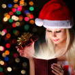 Christmas Miracle. Happy Blonde Girl with Santa Hat Opening Gift — Stock Photo #36681951
