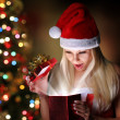 Christmas. Happy Blonde Girl with Santa Hat Opening Gift Box ove — Stock Photo