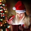 Christmas. Happy Blonde Girl with Santa Hat Opening Gift Box ove — Stock Photo #36745607