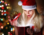 Christmas. Happy Blonde Girl with Santa Hat Opening Gift Box ove — Zdjęcie stockowe