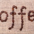 The word coffee made from coffee beans on burlap background — Stock Photo #37724925