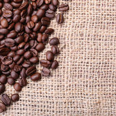 Кофейные зерна на фоне мешковины. — Стоковое фото