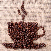 Coffee Beans, placed in shape of cup on linen or burlap — Stock Photo