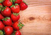 Jahody na dřevěné pozadí — Stock fotografie