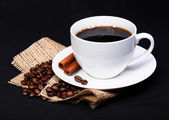 Coffee cup with saucer and coffee beans on burlap over black — Stock Photo