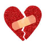 Broken Heart. Glitter ripped heart fixed with adhesive bandage — Stock Photo