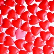 Foto Stock: Pink heart between a pile of red hearts. Candy Hearts background