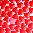 Pink heart between a pile of red hearts. Candy Hearts background — Stok fotoğraf