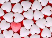 Pink heart between a pile of white hearts. Candy Hearts — 图库照片