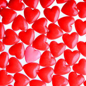 Pink heart between a pile of red hearts. Candy Hearts background — 图库照片