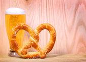 Beer Glass with German Pretzel on wooden background — Stockfoto