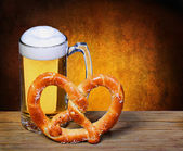 Beer Mug with German Pretzel on wooden table. isolated on white — Stock Photo