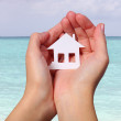 Stock Photo: Paper House in Female Hands over Tropical Beach. Concept