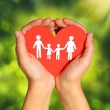 Paper Family and Heart in Hands over Green Sunny Background — Stock Photo #39033167