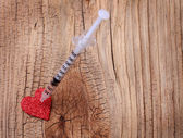 Glitter red heart and syringe with drug over wooden background. — Stock Photo