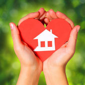 Paper House and Heart in Female Hands over Nature Green — Stock Photo
