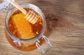Jar of honey with honeycomb and dipper on wooden background — Стоковое фото