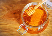 Jar of honey with honeycomb and dipper on wooden background — Stockfoto