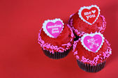 Chocolate cupcakes with red hearts, over red background. — Stock Photo