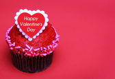 Chocolate cupcake with Valentines heart on the top, over red — Stock Photo