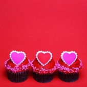 Chocolate cupcakes with Valentine hearts on the tops, over red — Stock Photo