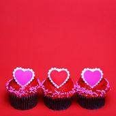 Bolinhos de chocolate com os corações dos namorados no topo, sobre vermelho — Foto Stock