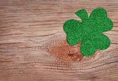 Shamrock over old wood background. Glitter Green Clover. — Stock Photo