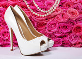 Bridal Shoes and Roses. White Heels over Hot Pink Flowers — Stock Photo