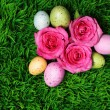 uovo di Pasqua colorate e rose rosa su erba verde — Foto Stock #41419053