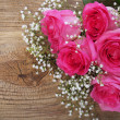 Stock Photo: Pink Roses and Gypsophilon Wooden Background