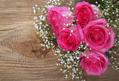 Pink Roses and Gypsophila on Wooden Background — Stock Photo