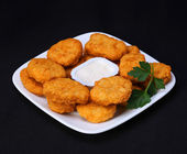 Chicken nuggets on plate with mayo over black background — Stock Photo