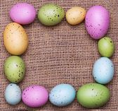 Colorful easter eggs on burlap background. Frame — Stock Photo