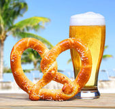 Beer Glass with German Pretzel over Beach View with Palms — Stock Photo