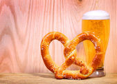 Beer Glass with German Pretzel on wooden background — Stock Photo