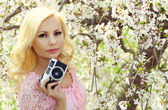 Blonde Girl with Retro Camera over Cherry Blossom — Stock Photo