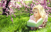 Girl reading the Book under Cherry Blossom. Blonde young woman — Zdjęcie stockowe