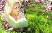 Blonde Woman with Book under Cherry Blossom. Beautiful girl — Stockfoto