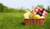 Picnic basket on green field — Stock Photo