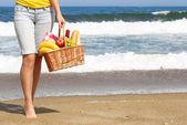 Picknick am Strand. weibliche Beine und Korb mit Essen — Stockfoto
