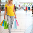Blonde Woman with Colorful Shopping Bags in Shopping Mall — Stock Photo #49291149