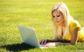 белокурая девушка с ноутбуком. улыбка красивая женщина, лежа на зеленой — Стоковое фото