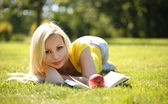 Blonde Girl with Book and Apple lying on Green Grass. Beautiful  — Foto de Stock