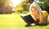 Blonde Girl with Book and Apple on Green Grass. Beautiful Woman  — Stock Photo
