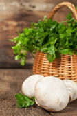 Mushrooms and a basket with fresh parsley — Stock Photo