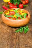 Salade met cherry tomaten, paprika's en rucola in een houten kom — Stockfoto