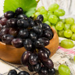Stock Photo: Fresh green and red grapes in a wooden bowl