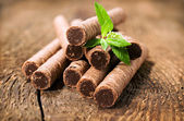 Chocolate wafer rolls with leaves of mint — Stock Photo