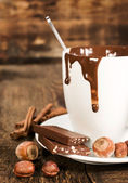 Cup of hot chocolate with nuts and cinnamon close-up — Stock Photo