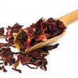 Wooden scoop with dry Sudanese rose petals — Stock Photo